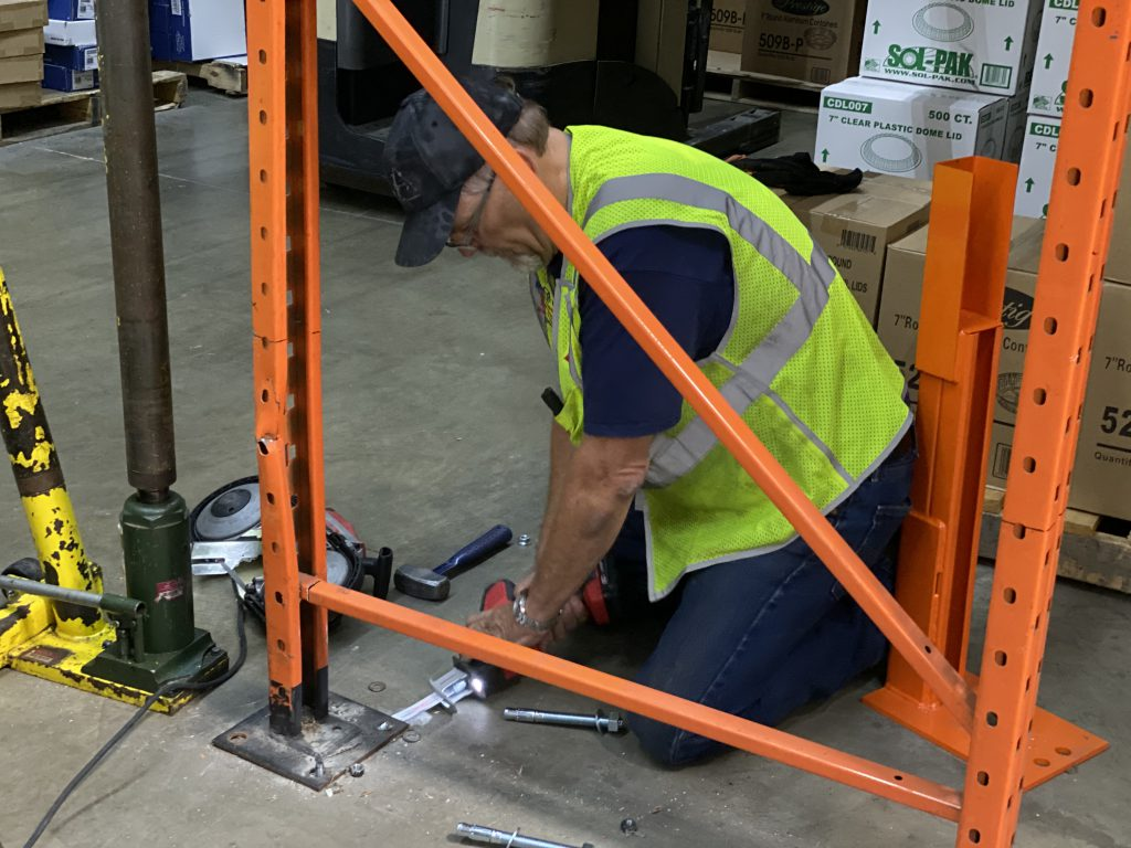 Rack repair specialist is cutting the anchor bolts underneath the pallet rack base-plate using a saws-all.