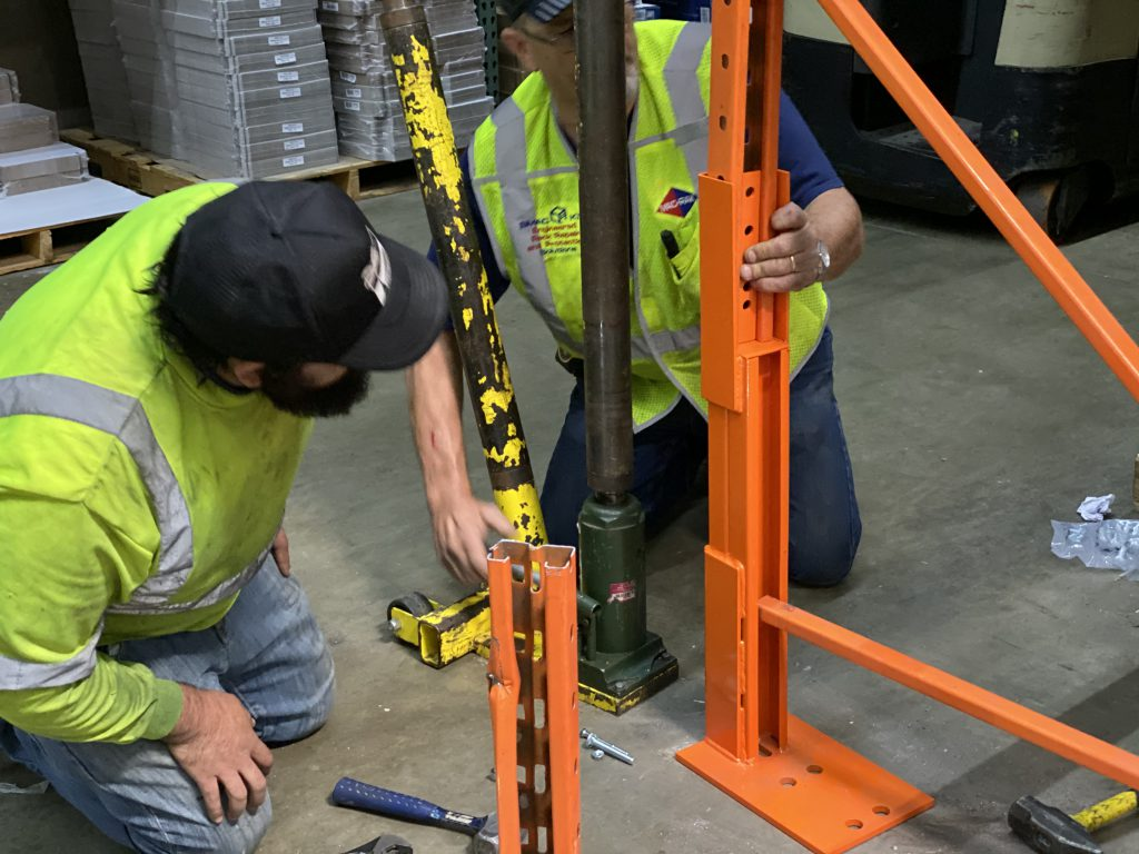 Rack repair kit is attached to pallet racking.  The damaged section of the racking is moved to one side.