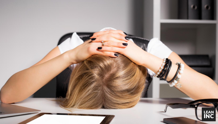 Sales manager frustrated with her head down on her desk